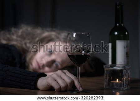 Young addicted depressed woman with red wine