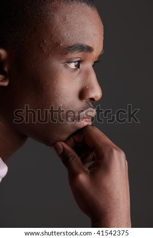 Young Adult black african businessman wearing a dark smart-casual outfit without a Jacket, on a dark grey background. Part of a series, Not Isolated. Single lights