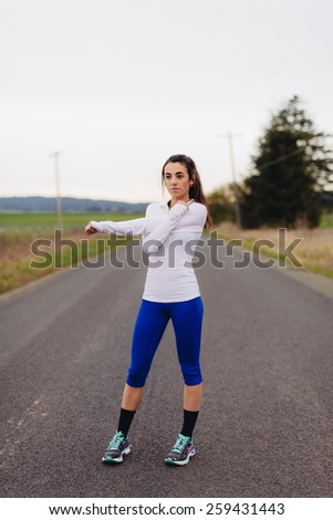 Young Adult Female stretching in Country Road