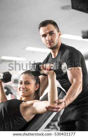 Young adult fitness couple. Woman doing chest and shoulder dumbbell  press on bench with personal coach assisting her and giving instructions.