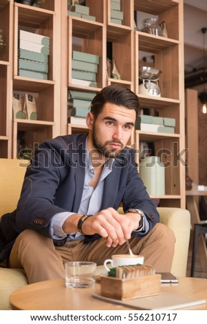 young adult handsome man stirring coffee cup indoors coffee bar indoors interior