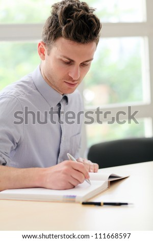 Young adult man writing notes with pen