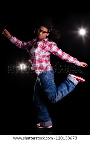 Young African American woman dancing, over black background