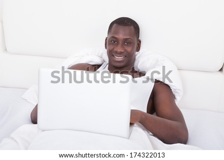 Young African Man Lying On Bed Using Laptop