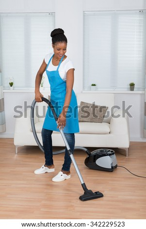 Young African Woman Cleaning Hardwood Floor With Vacuum Cleaner