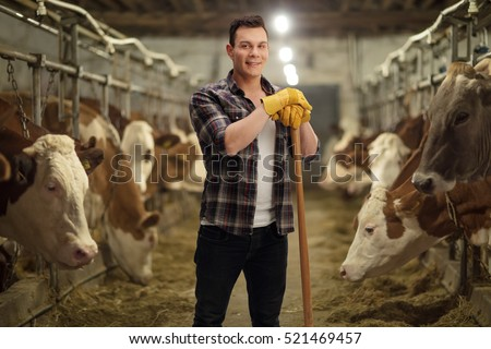 Young agricultural worker posing in a cowshed
