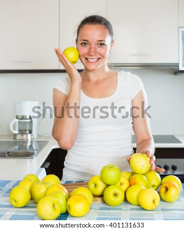 Young american woman cooking dish from apples in kitchen