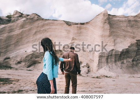 Young and beautiful couple walking near the stone cliffs