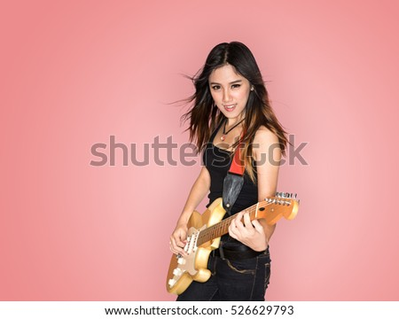 Young and beautiful rock girl playing the electric guitar on vintage background
