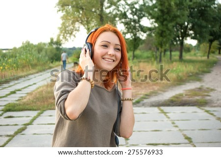 Young and beautiful woman wearing headphones listening to music and singing on the background of nature city park. Woman with headphones listening music. Music teenager girl dancing against.