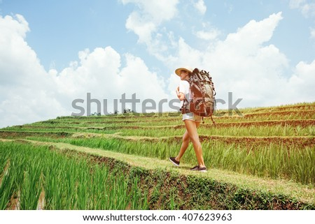 Young and fit traveling girl walking with backpack among rice terraces