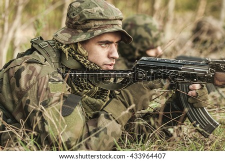 Young and handsome soldier pointing his rifle from cover, lying on ground