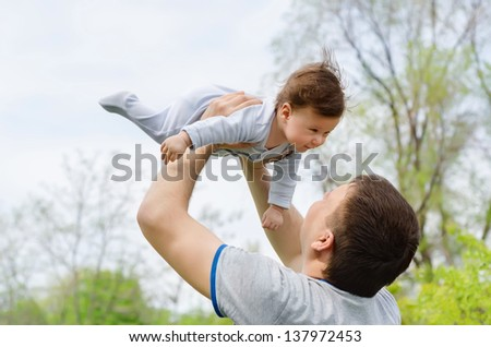 Young and happy father raising her baby in the park