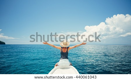 Young and happy woman traveling on the boat in the ocean