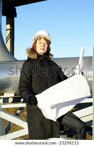 Young architect looking at blueprint in front of construction site against blue sky