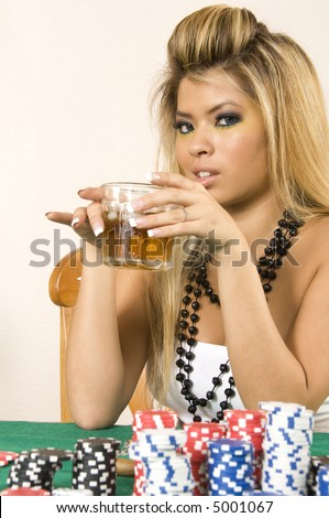 Young Asian-American blond woman with bare shoulders and long fingernails holds drink above poker table with chips (focus on her eyes)