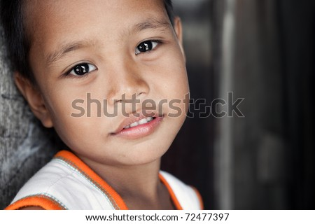 Young Asian boy with soft smile living in poverty stricken area - portrait against wall. Manila, Philippines.