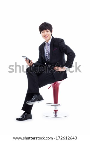 Young Asian business man using a pad PC sitting on the chair isolated on white background.
