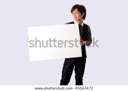 Young Asian business student man standing holding a white blank board and looking at it, isolated.