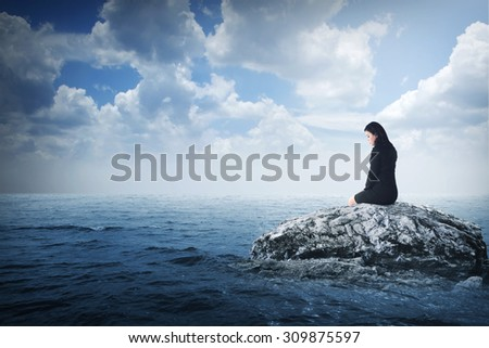 Young asian business woman sitting on the rock in the middle of the sea