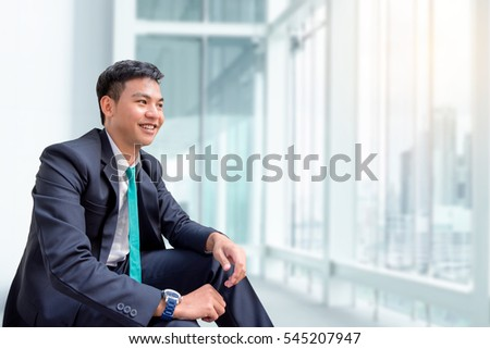 Young asian businessman sitting and looking out the window