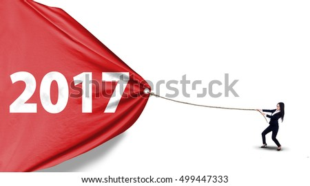 Young Asian businesswoman pulling number 2017 on a red banner with a rope, isolated on white background