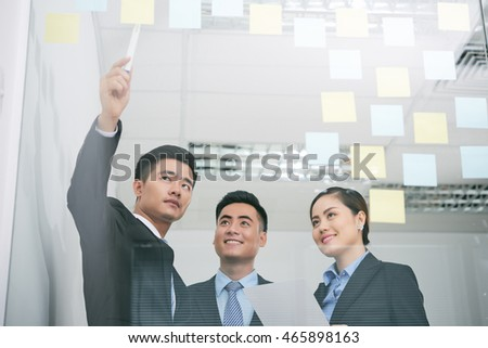 Young Asian entrepreneur explaining new strategy to his colleagues