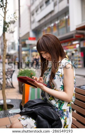 Young Asian girl checking e-mails with digital table at shopping street