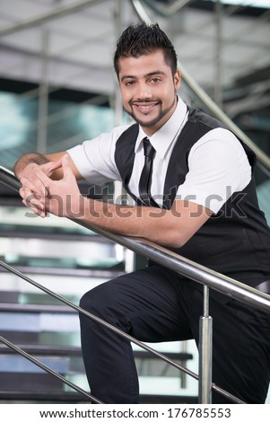 Young Asian Indian businessman standing on office background