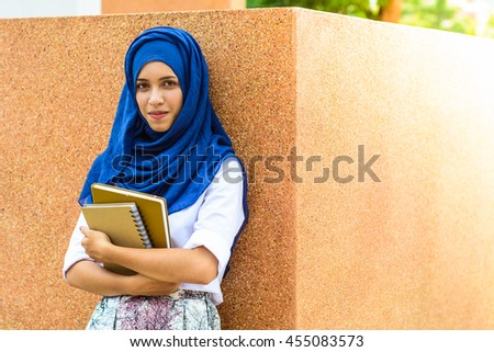 Young asian muslim woman holding notebook.