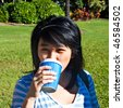 Young Asian woman drinking a cup of coffee from a blue cardboard cup in a park - stock photo