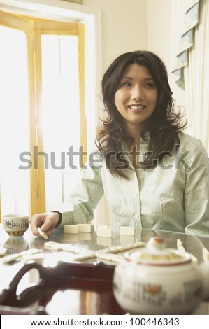 Young Asian woman playing dominoes