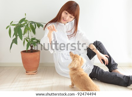 Young Asian woman playing with dachshund