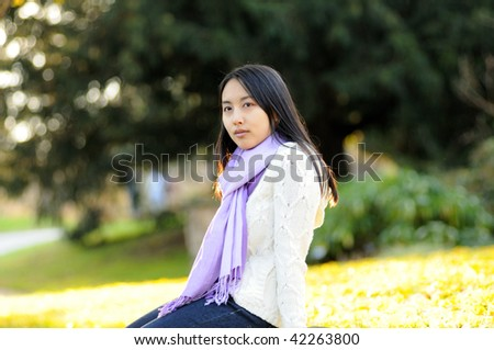 Young Asian woman sitting in front of bright autumn field