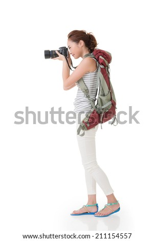 Young asian woman takes images with photo camera. Full length portrait. Isolated on the white background.