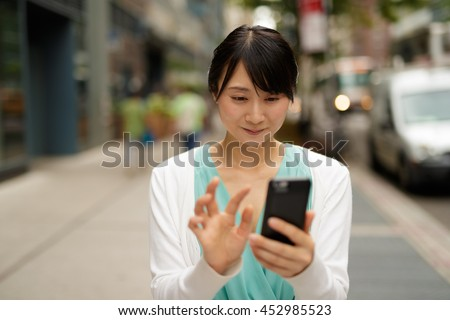 https://thumb10.shutterstock.com/display_pic_with_logo/1051921/452985523/stock-photo-young-asian-woman-walking-street-texting-cell-phone-452985523.jpg