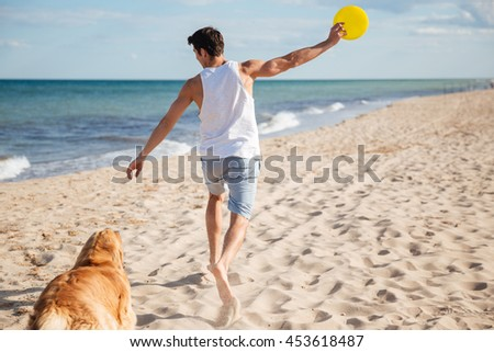 Young athletic handsome man playing with his dog on the beach