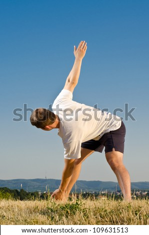 Young athletic men exercise on a field against blue sky