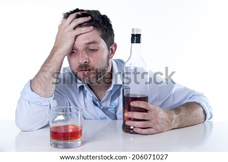 young attractive alcoholic business man with beard  wearing blue shirt and tie drunk and drinking  Scotch or Whisky looking wasted on office desk at work isolated on white background