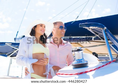 Young, attractive and rich couple have a party on a luxury sailing boat at summer
