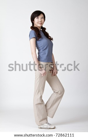 Young attractive Asian woman, full length portrait on gray studio background.