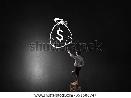 Young attractive businesswoman standing on chair and reaching money bag