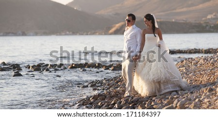Young attractive caucasian couple walking long pebble beach