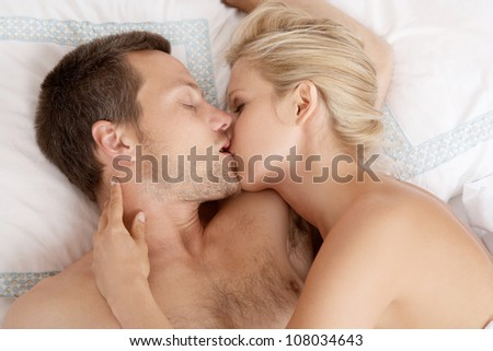 Young attractive couple kissing in bed.