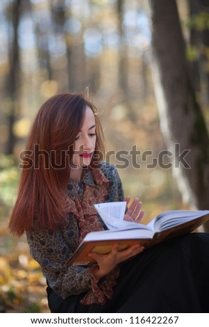 Young attractive girl reading a book in autumn park