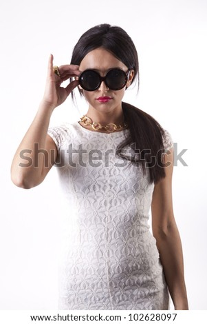 Young attractive  glamorous sexy woman in white dress holding her sunglasses