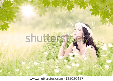 Young attractive happy woman blowing bubbles on the meadow