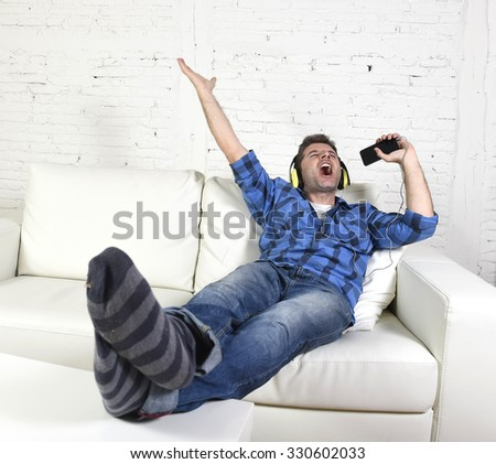 young attractive 20s or 30s man having fun alone lying on home couch listening to music holding mobile phone as microphone using headphones singing passionate happy and crazy