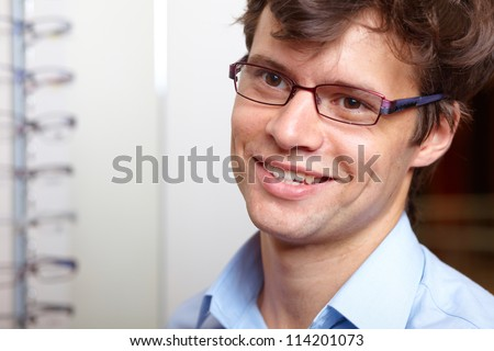 Young attractive smiling man at optician with glasses, background in optician shop