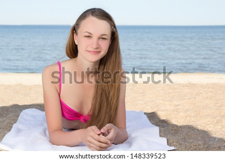 young attractive woman in pink bikini lying on the beach